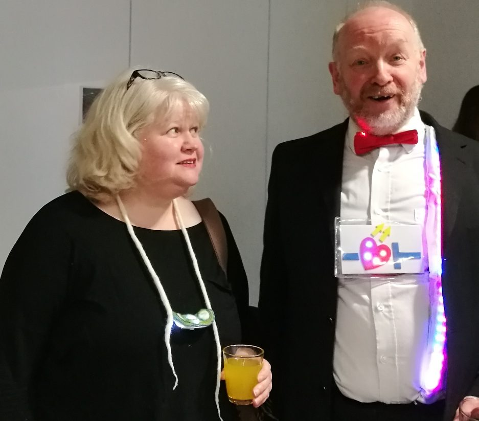 Caroline Kelly wearing her necklace made with handmade felt, slices of stalactite and LEDs next to Richard Millwood wearing his LED lit bowtie, braces and beating 'LED by the heart' decoration